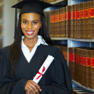A student wearing graduation attire in library